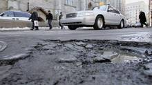 Motorists steer past a pothole on a Montreal street on March 24, 2005. The mayor is asking citizens whether to pave or not to pave city potholes. (PAUL CHIASSON/THE CANADIAN PRESS)