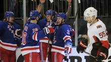 The New York Rangers celebrate a goal by Marc Staal, hidden, as Ottawa Senators' Sergei Gonchar skates past during the first period in Game 7 of their NHL Eastern Conference quarter-final playoff hockey game in New York, April 26, 2012. (RAY STUBBLEBINE/REUTERS)