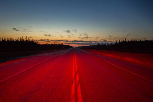 Highway 63 at dawn, lit by emergency vehicle lights.