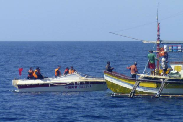 In this Feb. 27, 2015, photo provided by Filipino fisherman Renato Etac, Chinese Coast Guard members approach Filipino fishermen near Scarborough Shoal in the South China Sea.