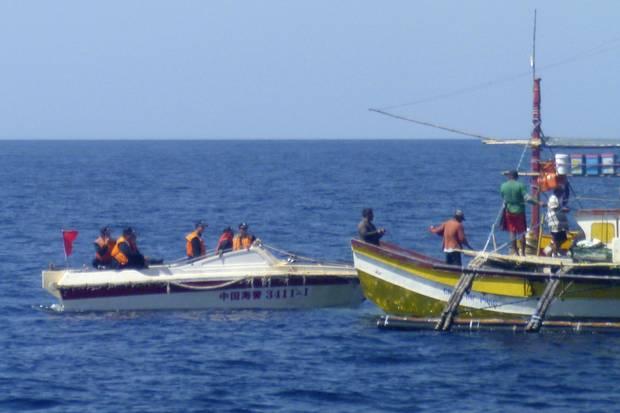 In this Feb. 27, 2015, photo provided by Filipino fisherman Renato Etac, Chinese Coast Guard members approach Filipino fishermen near Scarborough Shoal in the South China Sea.