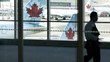 A person walks by Air Canada planes at Toronto Pearson Airport. (Michelle Siu/THE CANADIAN PRESS)