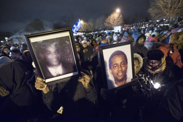 Mourners hold up photos of the mosque-shooting victims on Jan. 30, 2017, in Quebec City.
