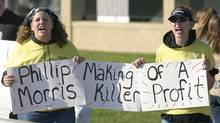 Protesters make their point as a car drives into the Philip Morris cigarette manufacturing plant in Richmond, Va., Thursday, April 24, 2003. Philip Morris' parent company, Altria Group, Inc., was holding its annual meeting inside. (WAYNE SCARBERRY/AP)