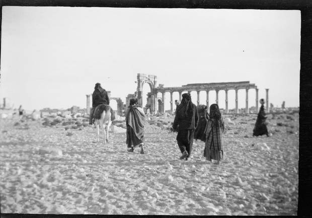 People walk past the ruins of Palmyra some time between 1925 and 1946.
