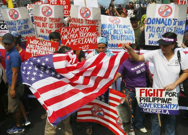 Protesters burn a mock U.S. flag and a real one during a rally at the U.S. embassy in Manila on Inauguration Day. Left-wing and Muslim activists have asked President Rodrigo Duterte in a noisy protest to keep his promise of charting a foreign policy independent of the United States by staying away from Mr. Trump.