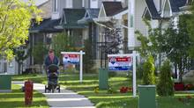 A woman pushes a stoller past for-sale signs in Fort McMurray, Alta.,on Aug.29, 2010. (Kevin Van Paassen/Kevin Van Paassen/The Globe and Mail)