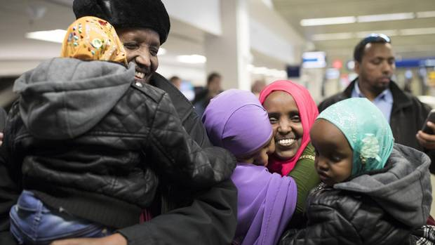 Mohamed Iye holds his 4-year-old daughter, Nimo, after being reunited with his wife, Saido Ahmed Abdille, centre right, and their other daughter Nafiso, 2, at Minneapolis' Saint Paul International Airport near Bloomington, Minn., after arriving from Amsterdam on Sunday.