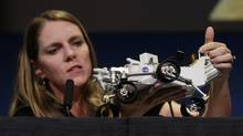 Jennifer Trosper, Mars Science Laboratory (MSL) mission manager, points out the communications antenna on a model of NASA's Mars science rover Curiosity as she speaks during a news conference at NASA's Jet Propulsion Lab in Pasadena, California August 6, 2012. (FRED PROUSER/REUTERS)