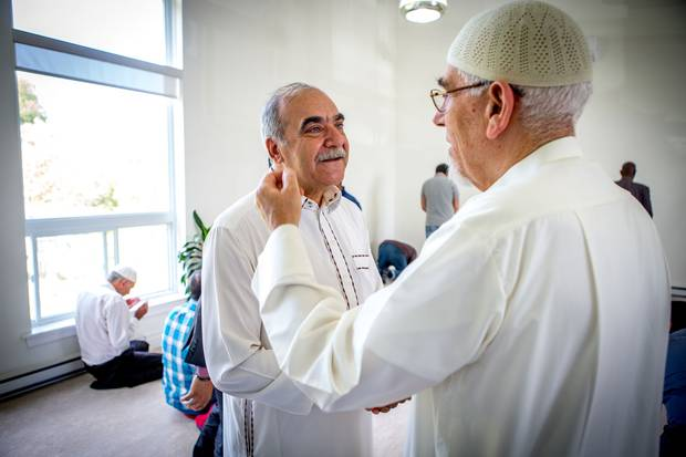Mr. Sharbaji speaks with the mosque's imam after prayers.