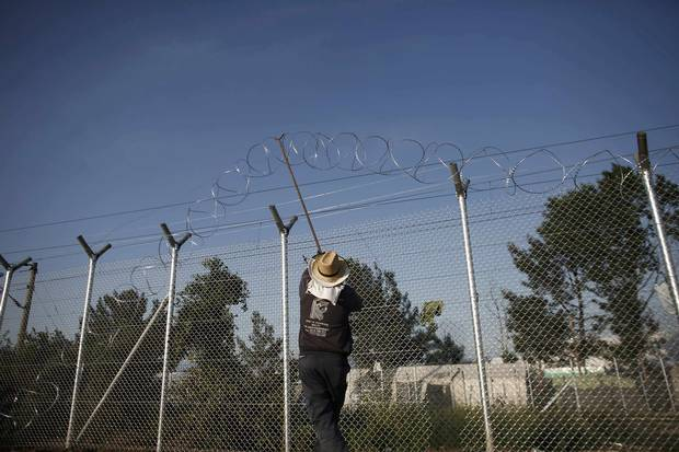 A worker places barbed wire on a fence at the Greek-Macedonian border.
