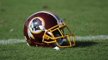 "A Washington Redskins football helmet lies on the field during NFL football minicamp. The U.S. Patent Office ruled the nickname is ""disparaging of Native Americans"" and that the team's federal trademarks for the name must be canceled. (Nick Wass/AP)"