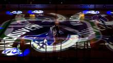 A worker moves a hockey net as Vancouver Canucks team logos are projected on the ice before the team's NHL hockey game against the Detroit Red Wings in Vancouver, B.C., on Thursday February 2, 2012 (The Canadian Press)