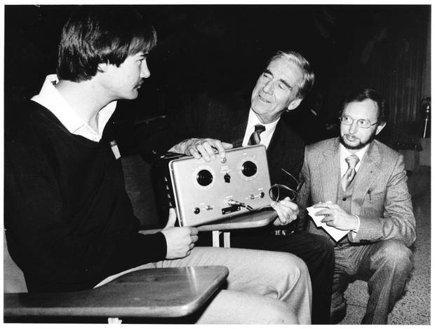 Dr. Wilfred Bigelow, centre, explains the workings of the first pacemaker, which he co-invented at the University of Toronto's Banting Institute in 1950, to two pacemaker users in October, 1982.