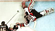 Buffalo Sabres' goalie Dominik Hasek sprawls to stop a shot by Pittsburgh Penguins' center Wayne Primeau (15) with help from Sabres' defenseman Dimitri Kalinin during the first period of playoff action, April 26, 2001 at the HSBC Arena in Buffalo, New York. (Reuters)