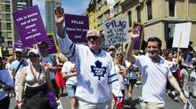 Toronto Maple Leafs general manager Brian Burke, centre, walks with comedian Rick Mercer, right, during the Gay Pride Parade in Toronto in 2011. (Mark Blinch/reuters/Mark Blinch/Reuters)