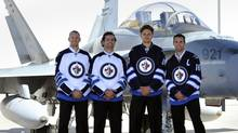 Winnipeg Jets players Eric Fehr (L-R), Mark Stuart, Nik Antropov and Andrew Ladd wear their new NHL jerseys in front of a CF-18 fighter jet during an event unveiling their new uniforms in Winnipeg September 6, 2011. REUTERS/Fred Greenslade (FRED GREENSLADE)