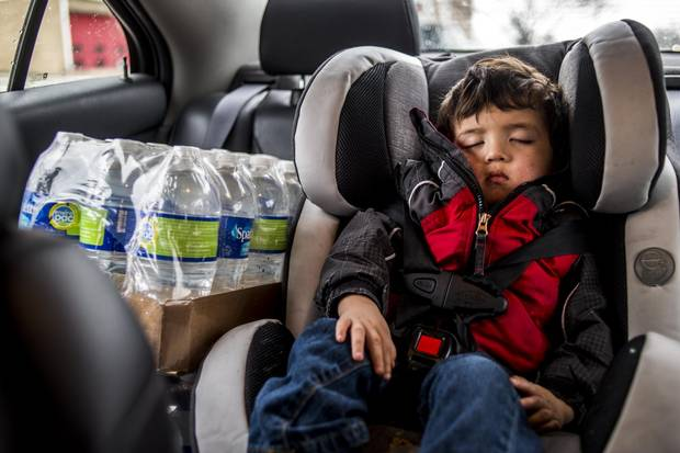 Liam Briones sleeps in a car seat as his father drives around from fire station to fire station gathering water for the week.