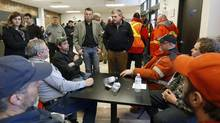 New Brunswick Premier David Alward, middle, speaks to emergency workers at Tobique-Plex arena in Plaster Rock, N.B., on Jan. 8, 2014. Plaster Rock residents had been evacuated the night before due to a train derailment and fire. (MATHIEU BELANGER/REUTERS)