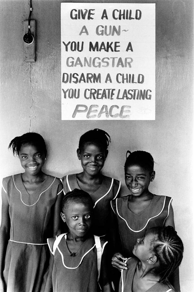 Children in school uniform pose in front of a poster promoting peace and disarmament. Sierra Leone, 1999.