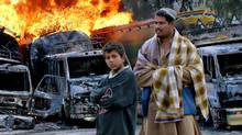 Bystanders pose in front of Afghanistan-bound NATO oil tankers set on fire by militants at the Pakistani border post of Torkham on March 4, 2011. (Qazi Rauf/AP)