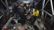 Men carry the body of a woman killed in a stampede on a railway platform at the main railway station in Allahabad, India, Feb. 10, 2013. (Kevin Frayer/AP)