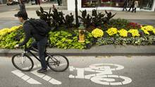 A cyclist pedals along in traffic on Bloor Street near Yonge Street in Toronto (2013 file photo) (Peter Power/The Globe and Mail)