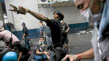 An anti-government Red Shirt protester launches a slingshot loaded with a large firecracker toward Thai soldiers as clashes continued in Bangkok on Monday. (Getty Images)