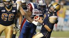 Winnipeg Blue Bombers' quarterback Alex Brink (7) is hit hard and sacked by Montreal Alouettes' Rod Davis (12) during the second half of their CFL game in Winnipeg, Friday, August 3, 2012. (John Woods/THE CANADIAN PRESS)
