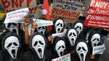 Activists wearing masks protest against nuclear energy in Manila on March 15. (TED ALJIBE/AFP/Getty Images)