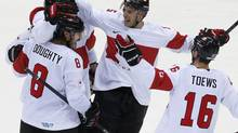 Canada's Shea Weber, hidden, celebrates his goal against Latvia with teammates Drew Doughty (8), Dan Hamhuis, and Jonathan Toews during the third period of their men's quarter-finals game at the 2014 Sochi Winter Olympic Games, February 19, 2014. (JIM YOUNG/REUTERS)