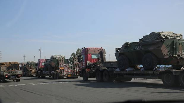 Military equipment moves down a highway in Xinjiang, where the Chinese government has responded with a massive display of force to what it calls extremist activity in the area.