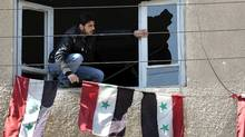 "A Syrian security man, sets Syrian flags through a broken window of the anti-drug police office that was destroyed by Syrian anti-government protesters, in the southern city of Daraa, Syria, Monday March 21, 2011. Mourners chanting ""No more fear!"" have marched through a Syrian city where anti-government protesters had deadly confrontations with security forces in recent days. The violence in Daraa, a city of about 300,000 near the border with Jordan, was fast becoming a major challenge for President Bashar Assad, who tried to contain the situation by freeing detainees and promising to fire officials responsible for the violence. (Hussein Malla/Hussein Malla/AP)"