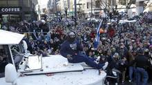 Seattle Seahawks' running back Marshawn Lynch throws pieces of candy while riding on the hood of a vehicle during the Super Bowl champions parade, Wednesday, Feb. 5, 2014, in Seattle. (Ted S. Warren/AP)