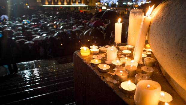 Candles are placed outside the Vancouver Art Gallery as hundreds of people honour the victims of the Paris terrorist attacks in Vancouver on Nov. 14, 2015.