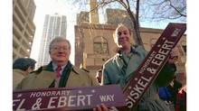 "Ebert, left, and Gene Siskel hold signs marking ""Siskel & Ebert Way"" in Chicago on Wednesday, Feb. 1, 1995. The City of Chicago honored the critics by giving a city street the honorary title. (Bill Stamets/The Associated Press)"