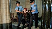 A climate-change protester is dragged out of the House of Commons after disrupting Question Period on Monday, October 26, 2009. (Sean Kilpatrick)