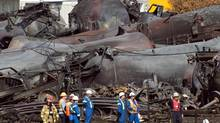 Workers stand before mangled tanker cars at the crash site of a train derailment and fire in Lac-Megantic, Quebec, in this Tuesday, July 16, 2013 file photo. (Ryan Remiorz/THE CANADIAN PRESS)