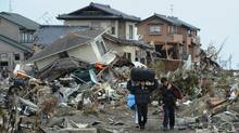 Residents carry belongings from tsunami devastated homes in Natori City, Miyagi prefecture on March 14, 2011. (Mike Clark/AFP/Getty Images/Mike Clark/AFP/Getty Images)