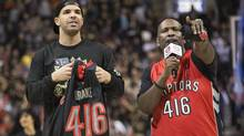 Rapper Drake holds a shirt bearing his name and Toronto's area code during a break in the Toronto Raptors-Brooklyn Nets NBA basketball game in Toronto. (CHRIS YOUNG/THE CANADIAN PRESS)