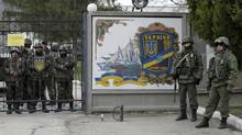 Ukrainian soldiers, left and unidentified gunmen, right, guard the gate of an infantry base in Privolnoye, Ukraine, Sunday, March 2, 2014. Hundreds of unidentified gunmen arrived outside Ukraine's infantry base in Privolnoye in its Crimea region. (Darko Vojinovic/AP)