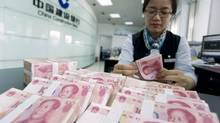 A clerk counts 100-yuan banknotes at a branch of China Construction Bank in Hai'an in China's Jiangsu province on Tuesday, June 10. (CHINA DAILY/REUTERS)