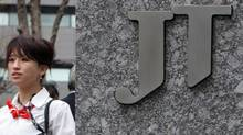 A woman walks past the Japan Tobacco Inc. (JT) headquarters in Tokyo in this file photo. (TOSHIYUKI AIZAWA/REUTERS)