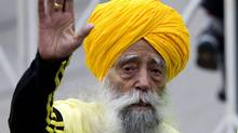 One-hundred-year-old Fauja Singh (left) runs with deputy coach at the start of the Toronto Waterfront marathon on Sunday October 16, 2011. THE CANADIAN PRESS/Chris Young. (Chris Young)