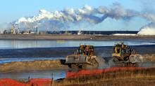 Workers use heavy machinery in the tailings pond at the Syncrude oil sands extraction facility near Fort McMurray. (MARK RALSTON/AFP/Getty Images)