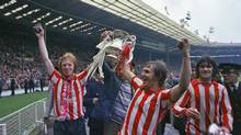 Sunderland's Mike Horswill, left, Ian Porterfield, centre, and Billy Hughes, right, take a victory lap around Wembley Stadium, London, in this May 5, 1973 file photo, after their 1-0 win against Leeds United in the FA Cup final. Porterfield's goal gave Sunderland the honor of being the first Second Division team to win the trophy since the 1930s. (The Associated Press)