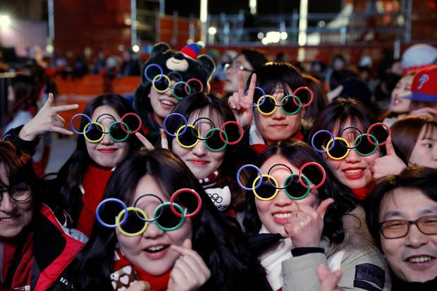 Volunteers pose for photographs during a medal ceremony at the Medal Plaza in Pyeongchang, on Feb. 18, 2018.