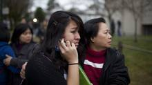 A student is embraced by a family member outside Sir Charles Tupper Secondary School in Vancouver after a teenage girl said she was stabbed. The story, which turned out to be bogus, caused the school to go into lockdown on Jan. 9, 2012. (Rafal Gerszak For The Globe and Mail/Rafal Gerszak For The Globe and Mail)