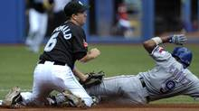 Toronto Blue Jays' shortstop John McDonald (L) tags out Texas Rangers' base runner Endy Chavez trying to steal second base during the first inning of their MLB American League baseball game in Toronto July 31, 2011. REUTERS/Mike Cassese (Mike Cassese/Reuters)