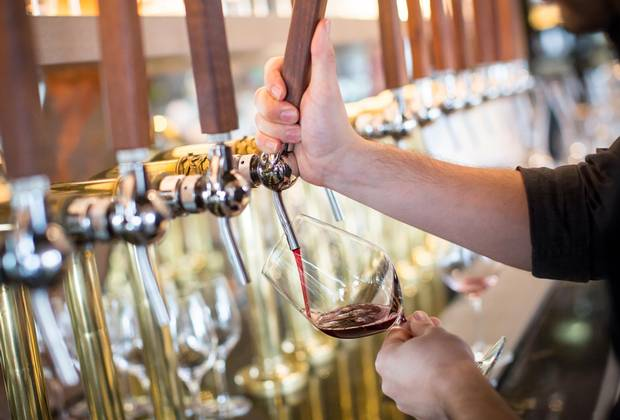 Darcy Golby pours a glass of red wine from the taps at Provence Marinaside.